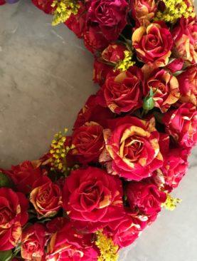 Coroncina funebre di roselline rosse